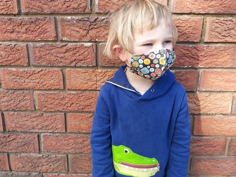 Child standing against wall wearing face mask.