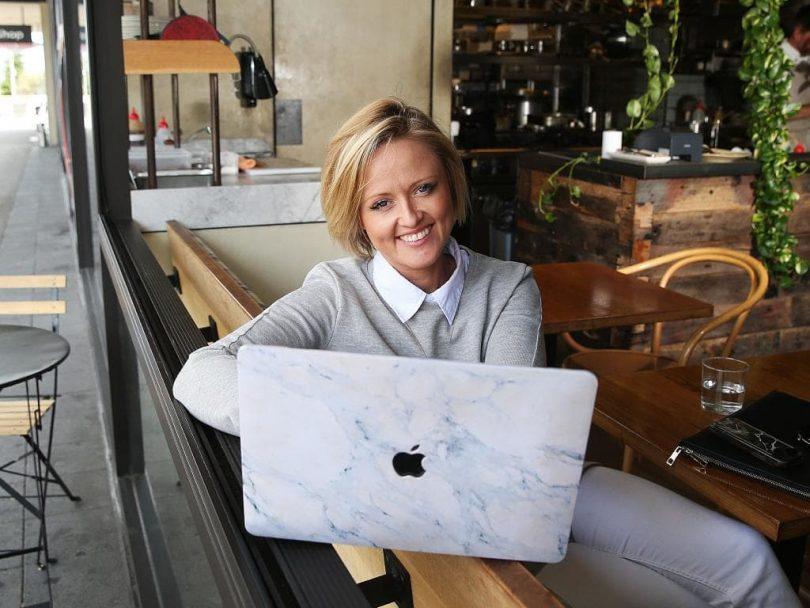 Jen Hollingsworth sitting at laptop in cafe.