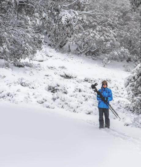 Michael Harris carrying his tripod through heavy snow.