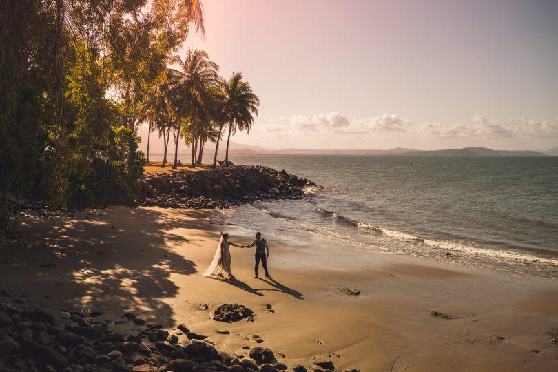 Jayde Theodore and Harri Colbert holding hands on beach.