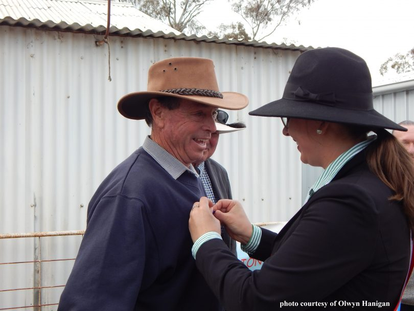 Bill West receiving pin from woman.