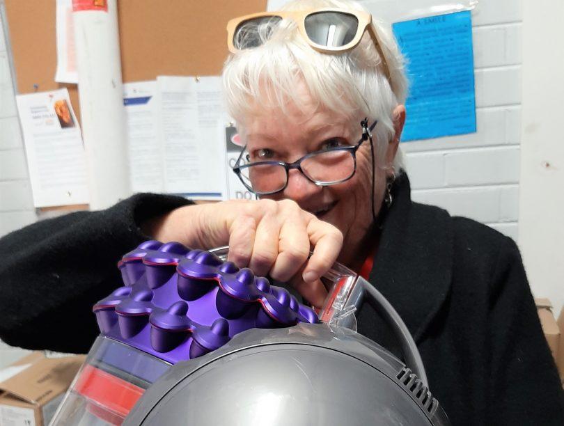 Caroline Long holding Dyson vacuum cleaner.