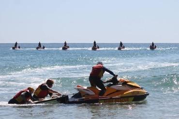 Surf lifesavers in training on jet ski.
