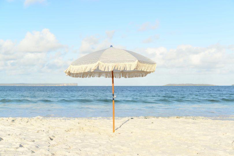 Umbrella in sand on deserted NSW South Coast beach.