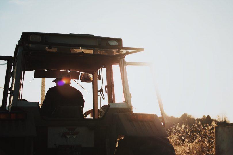 Farmer in tractor on farm.