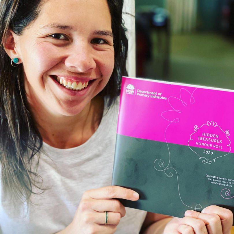 Carolina Merriman holding 2020 Hidden Treasures Honour Roll publication.