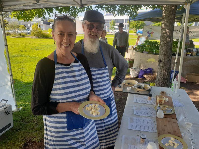 Lisa Kremmer and Wayne White holding cheese at their Bega Farmers Market stall.