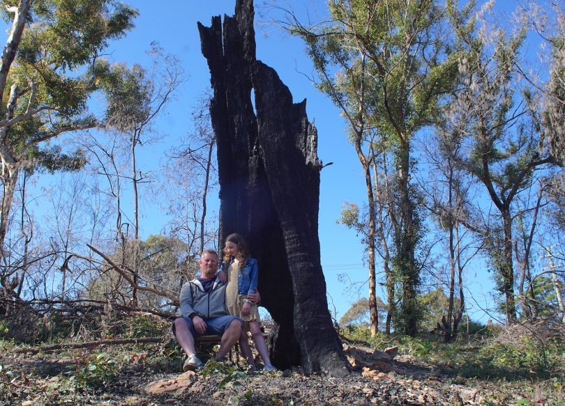 Jim Hughes and his daughter, Raeden, sitting next to burnt tree.
