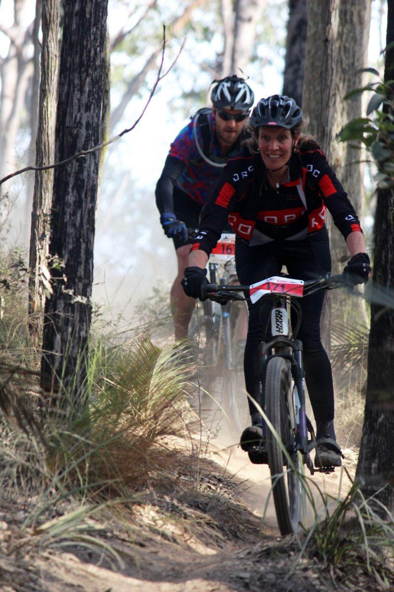 Woman and man mountain biking in bush.
