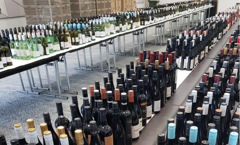 Hundreds of bottles of wine on tables.