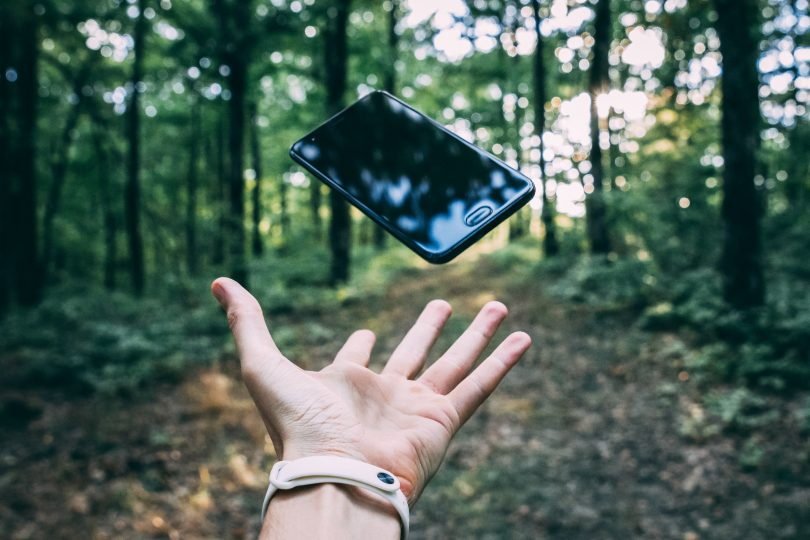 Hand throwing mobile phone in forest.