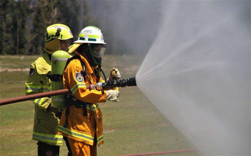 Girl holding fire hose.