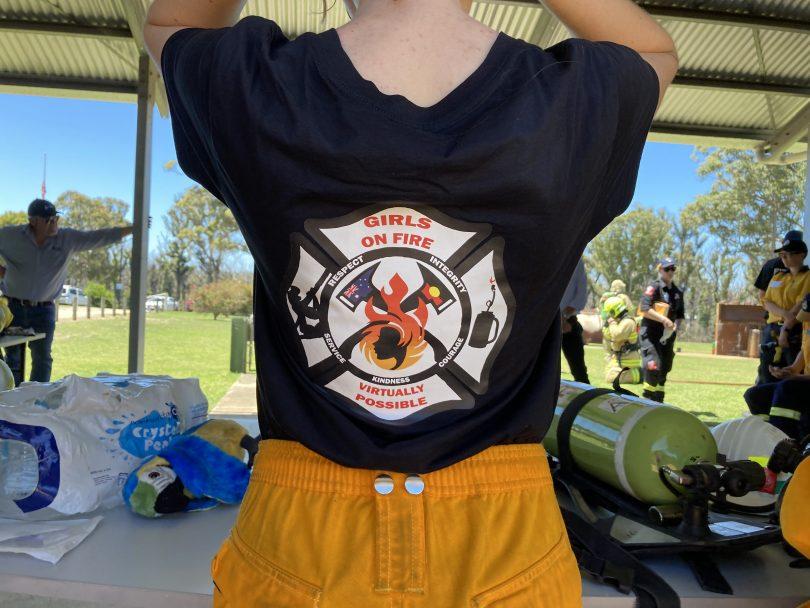 Girl showing Girls on Fire logo on back of T-shirt.
