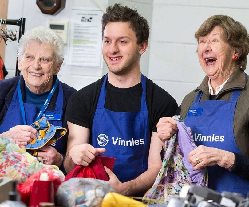 Three Vinnies workers holding donated items.