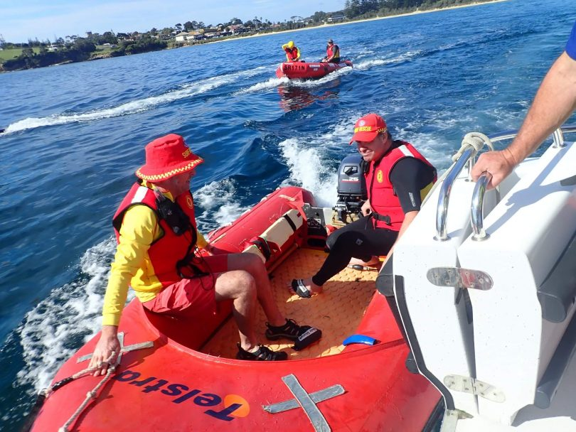 Surf lifesavers heading out to sea in boats.