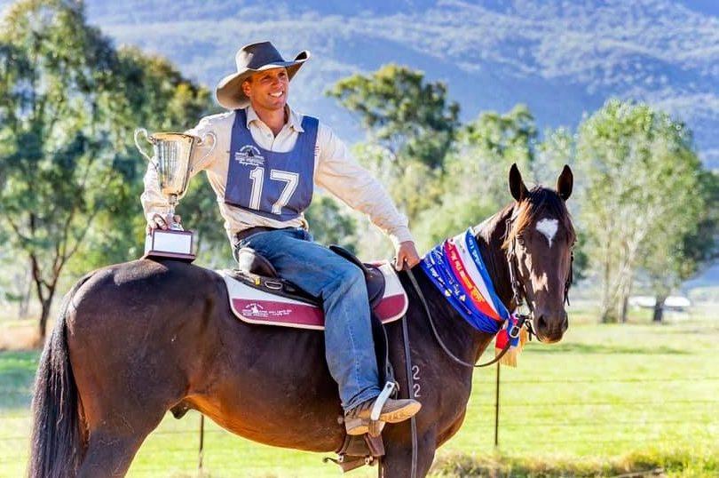 Kieran Davidson holding trophy on horseback.