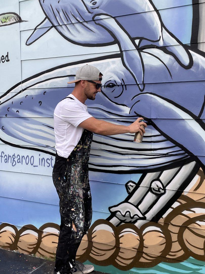 Don Paull spray painting a mural in Batemans Bay.
