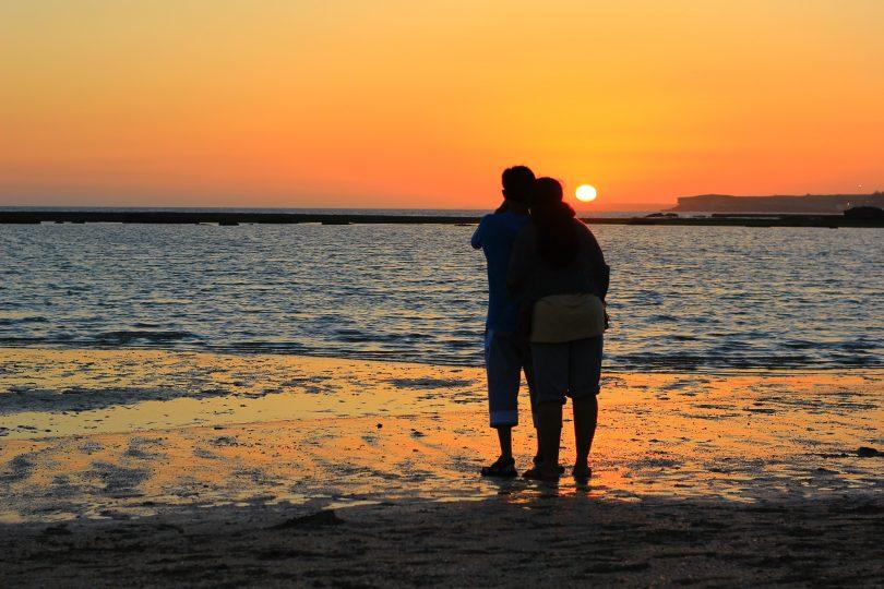 Romantic couple watching sunset on beach.