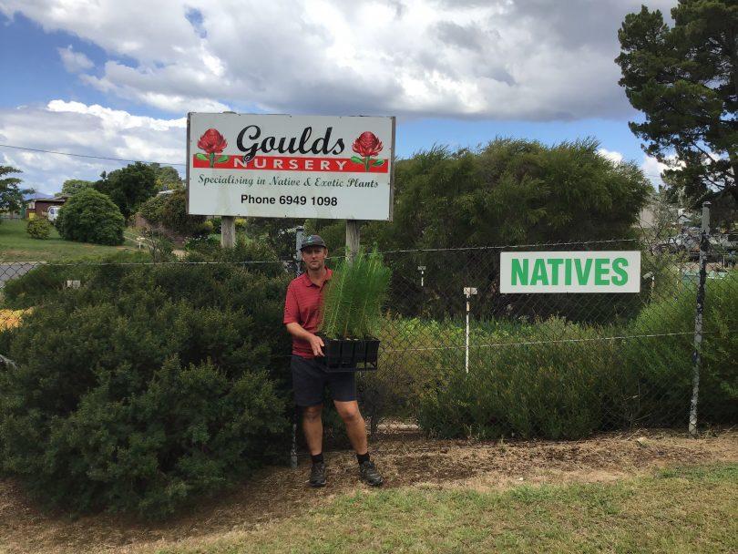 Jamie Gould holding seedlings outside Goulds Nursery in Batlow.
