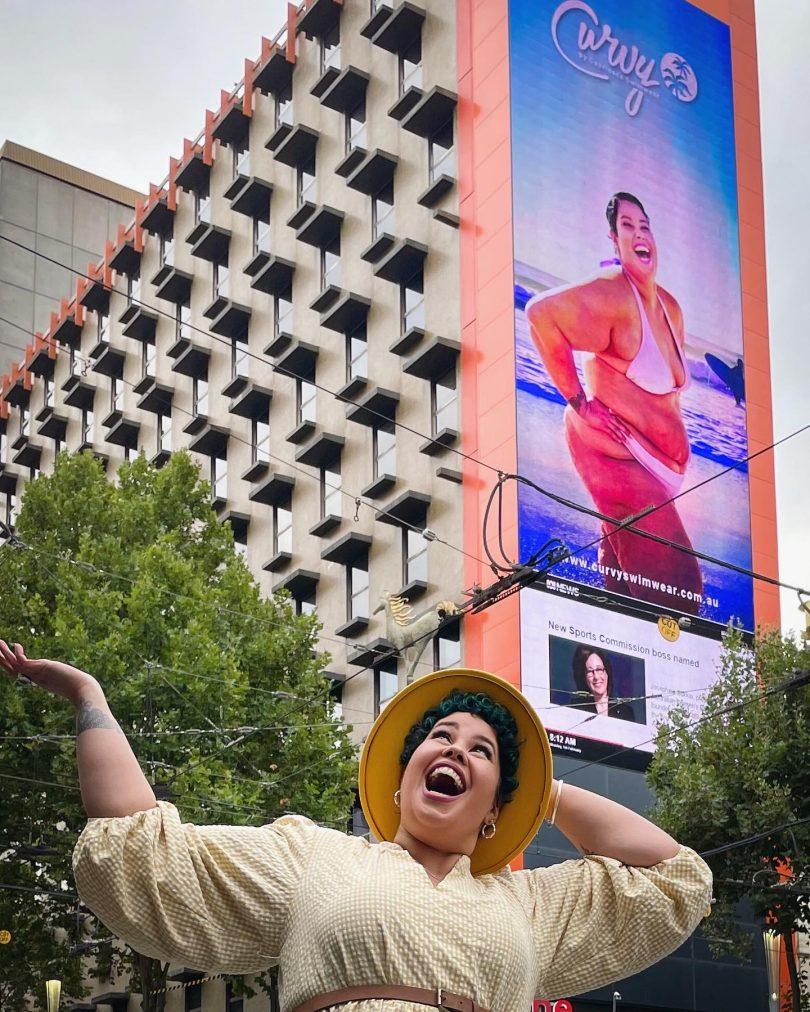 April Hélène-Horton stands under her billboard