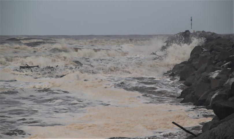 Sea foam on Moruya River at high tide after heavy rain.