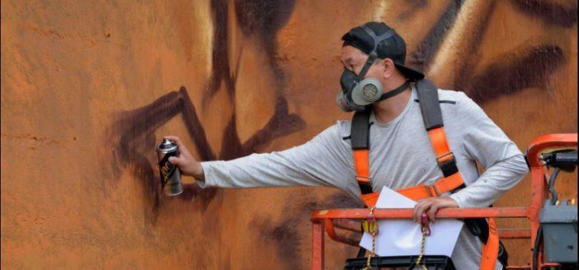 Artist Heesco working on mural on old flour mill silos at Harden-Murrumburrah.