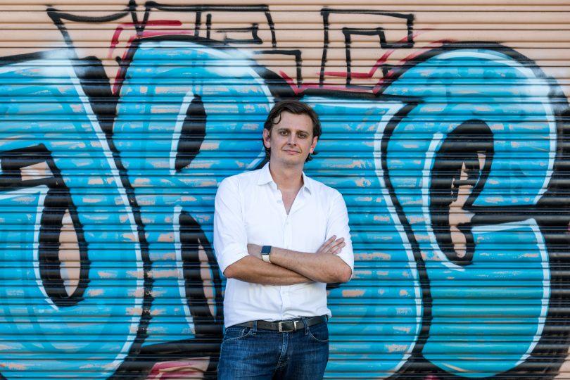 Anton Szpitalak standing in front of graffiti wall