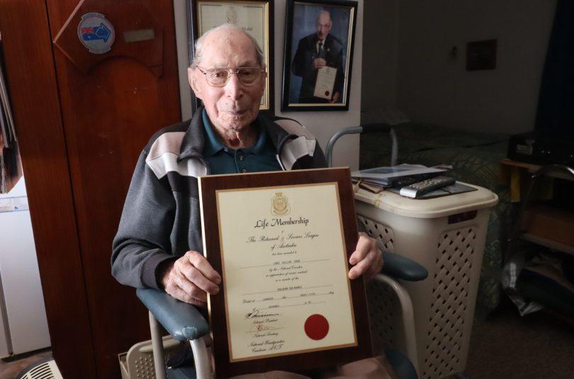 Lance Cooke holding framed certificate at home in Gunning