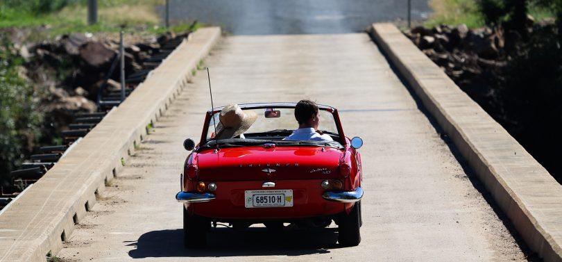 Classic convertible sports car driving across bridge