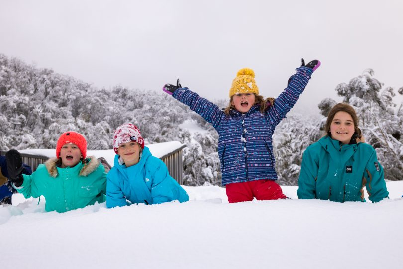 Four children playing in snow