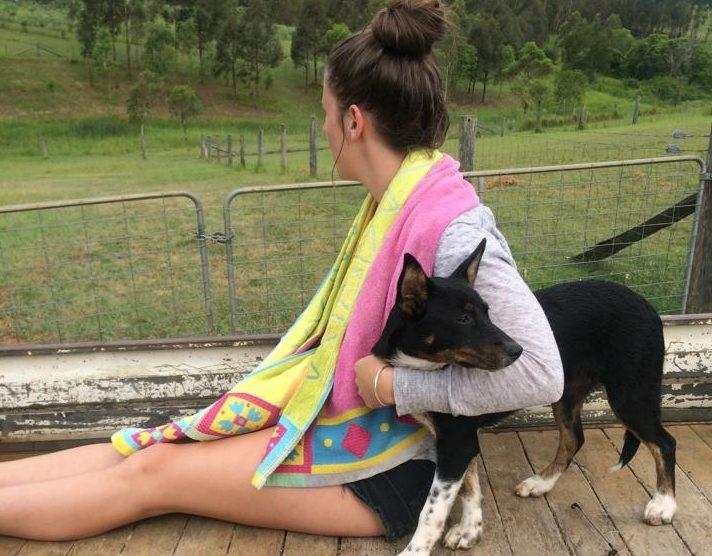 Hannah Sparks on a farm with dog