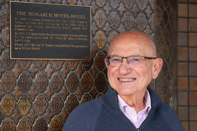 Michel Nader next to plaque at Monarch Hotel in Moruya