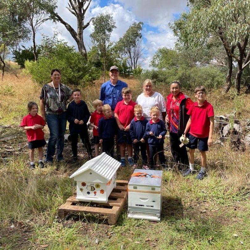 Binda Public School students with beekeeper, principal and hive