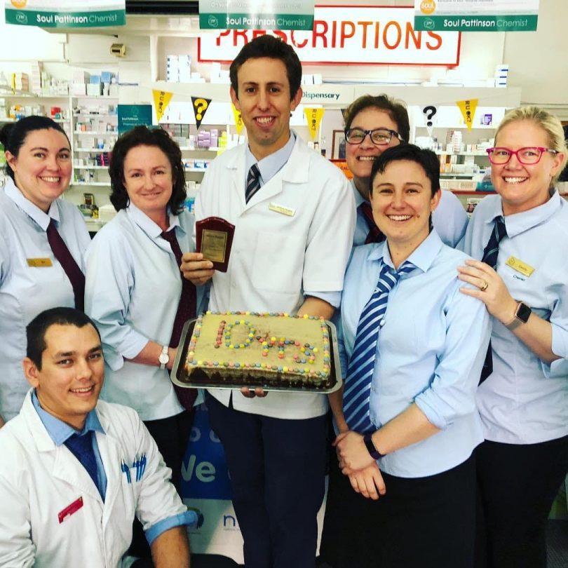 Andrew Douglas holding cake with Priceline Pharmacy Yass staff